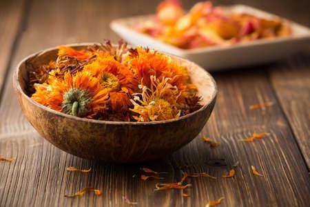 Homeopathische geneeskunde, calendula droge bloemen en houten oppervlak Stockfoto - 22487835
