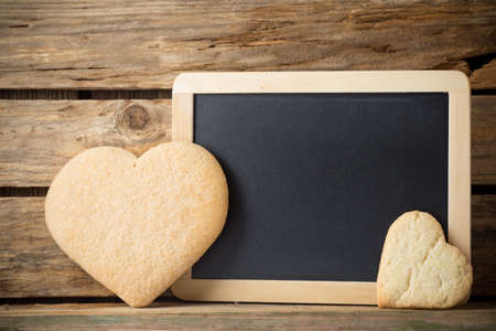Blackboard on wooden table with heart from the cookie. photo