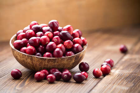 Cranberries in wooden bowl on wooden background. Reklamní fotografie - 23006085