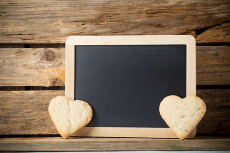 Blackboard on wooden background with heart from the cookie. photo