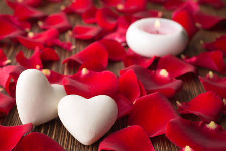 Rose petals and stone hearts. photo