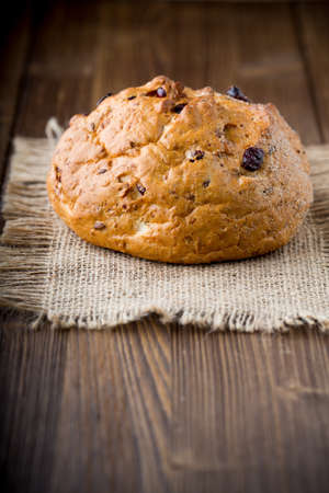 bakery products: Fresh bread with cranberries on a wooden background. Stock Photo
