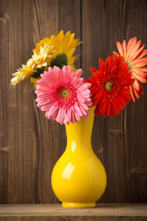 home accent: Gerbera flower on the vase, and the wooden background.