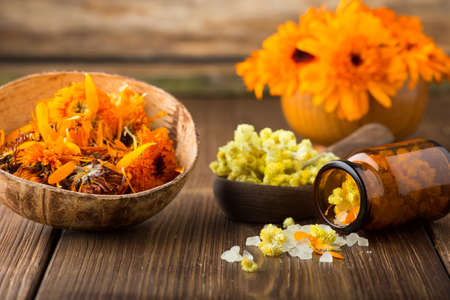 arvensis: Homeopathic medicine, calendula dry flowers and wooden surface.