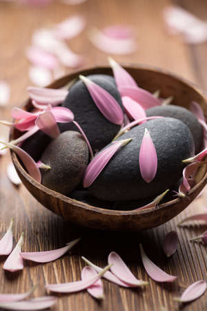 relaxion: Spa stones with flower petals. Relaxing massage.