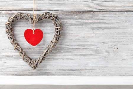 Braided wicker heart with a red heart in the middle on a wooden background. photo