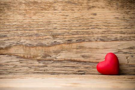 木製の背景に赤いハート。