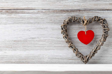 full willow: Braided wicker heart with a red heart in the middle on a wooden background.