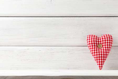 full willow: Fabric heart with a button on a white wooden background. Stock Photo