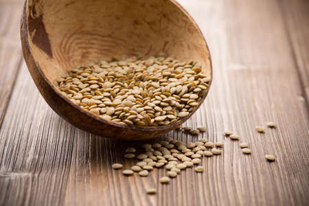 Lentils wooden bowl on wooden background. Healthy food. photo