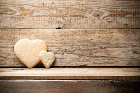 Heart-shaped biscuit on wooden background. photo
