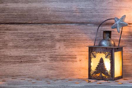 holiday lighting: Lantern, Christmas decor, wooden background. Stock Photo