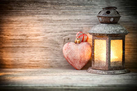 Lantern on a wooden table, a heart symbol. photo