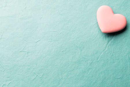 紙の背景にピンク ハート形のキャンディー。
