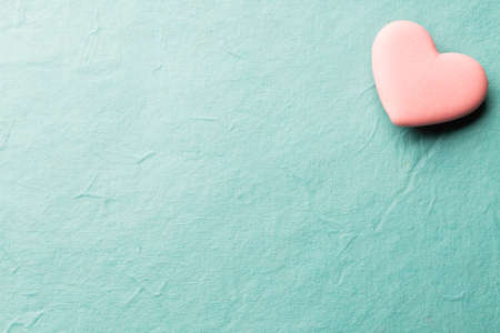 Pink heart-shaped candy on a paper background. Standard-Bild