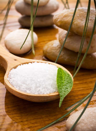 Sea salt in a wooden spoon with a green leaf, spa stones, drops of water. Reklamní fotografie