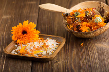 Homeopathic medicine, calendula dry flowers and wooden surface. photo
