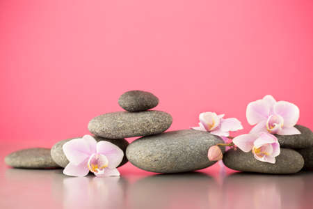 zen stones: Spa stones on pink background with orchids. Stock Photo