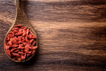 Goji berries on a wooden spoons, wooden brown background.