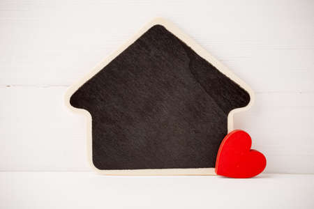 Board in the form of home on a white wooden background. photo