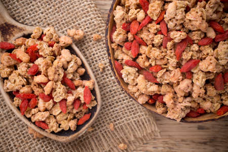 Muesli with goji berries in a bowl on a wooden background. photo