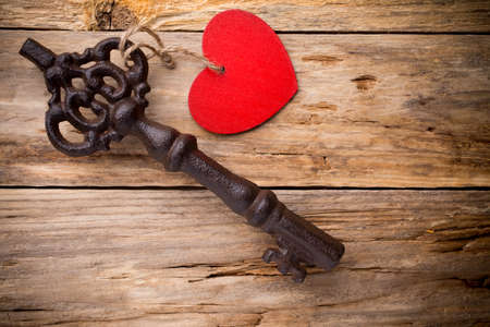 Old vintage key with heart on wooden . photo