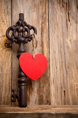 Old vintage key with heart on wooden background. photo