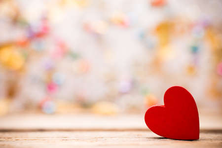 Red wooden heart on a wooden background with boke background. Stock Photo