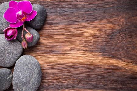 spa stone: Orchideenbl�te auf Holzuntergrund mit Wellness-Steine. Lizenzfreie Bilder