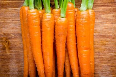 carrot: Zanahorias frescas en un fondo de madera. Foto de archivo