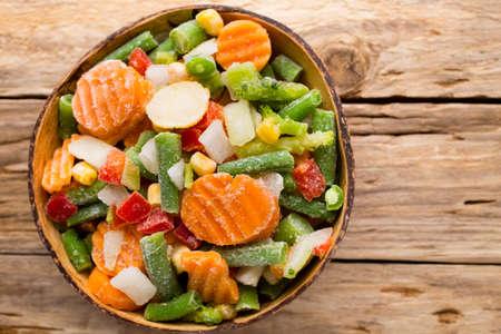 Frozen vegetables  in a wooden table. Zdjęcie Seryjne