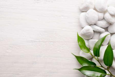 white pebble: White pebble stones and leafs Background. Stock Photo