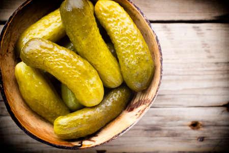 pickles: Pepinillos en recipiente de madera sobre la mesa