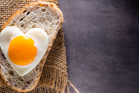 egg shape: Fried egg on heart-shaped slice of bread.
