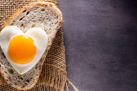 Fried egg on heart-shaped slice of bread.