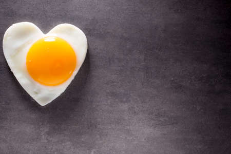 Fried egg heart-shaped and gray background.