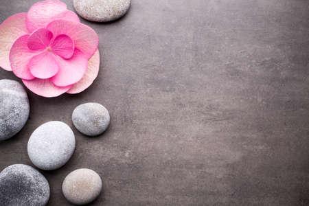 Close-up van spa stenen en bloem op een grijze achtergrond.