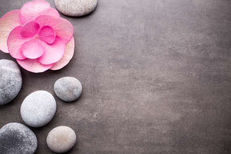 Close up view of spa stones and flower on grey background. Stock Photo