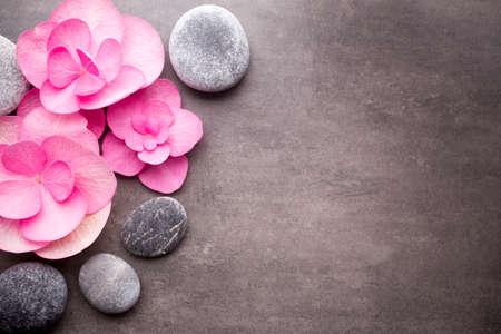 Close-up uitzicht op spa stenen met bloemen op grijze achtergrond. Stockfoto
