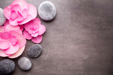 Close up view of spa stones with flowers on grey background.