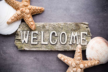 welcome to: Inscription welcome with marine accessories, starfish, shells.