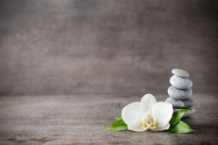 masoterapia: Piedras del balneario y orquídea blanca en el fondo gris.