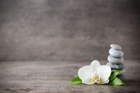 Massage therapy: Spa stones and white orchid on the grey background.