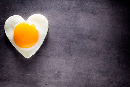 boiled: Fried egg heart-shaped and gray background.