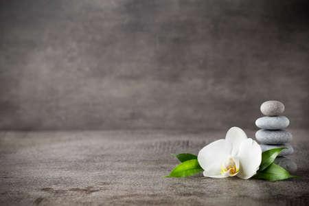 Spa stenen en witte orchidee op de grijze achtergrond. Stockfoto - 44143010