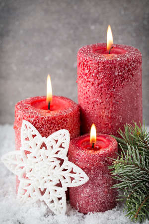 christmas decor: Three red candles on gray background, Christmas decoration. Advent mood. Stock Photo