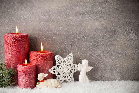 Drie rode kaarsen op een grijze achtergrond, kerstversiering. Advent stemming.