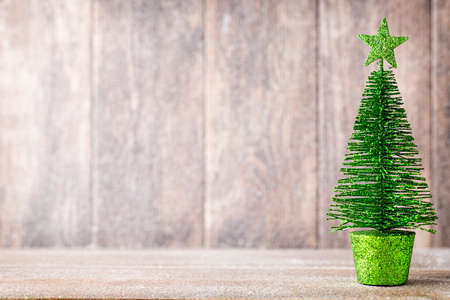holiday background: Golg and green christmas tree on a wooden background.