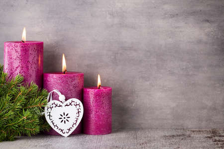 candlelight memorial: Three purple candles on gray background, Christmas decoration. Advent mood. Stock Photo