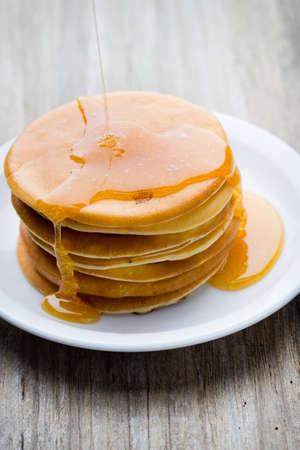 hot cakes: Pila de panqueques caseros con miel en el fondo de madera.